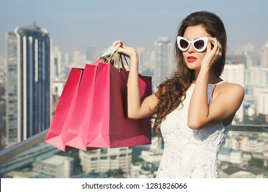 Beautiful and stylish woman with a shopping bags on roof of building in the big and modern city