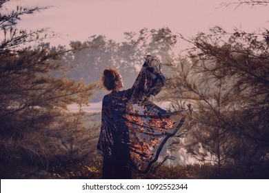 beautiful stylish woman silhouette wearing cape on sunset