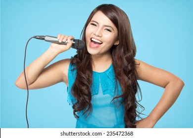 beautiful stylish woman singing karaoke isolated over blue background