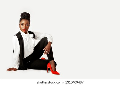 Beautiful stylish woman sitting with her knee propped up hand on her knee wearing a tussle waistcoat and red heels