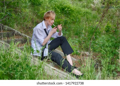 A beautiful and stylish woman with a slightly androgynous appearance with short blond hair (haircut), in a men's white shirt, black pants and tie, sits on the steps and lights a cigarette to smoke