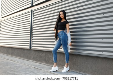 Beautiful stylish woman with sunglasses in fashionable clothes with white shoes is standing near a modern wall