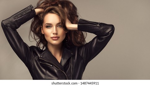 Beautiful stylish woman wearing  black leather jacket. Beautiful stylish woman тdressed in a black leather jacket. Fashionable and self-confident girl with long curly hair. Clothing, style and fashion