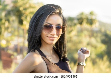 Beautiful stylish woman wearing sunglasses outdoors in resort location.