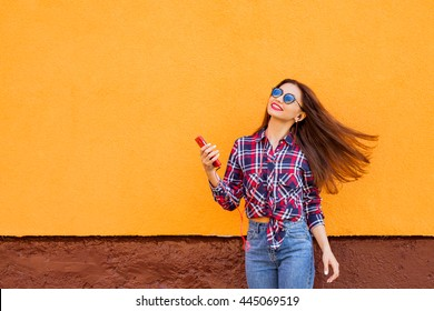 beautiful stylish women with smartphone and headphones. Flying hairs. Orange background. Copy-space