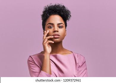 Beautiful stylish young African American woman with dark curly bushy hair enjoys summer rest, has serious and mysterious expression on face, poses in studio