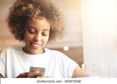Beautiful stylish young African woman with curly hair messaging friends using mobile phone, looking happy, smiling. Black student girl browsing Internet on electronic device, sitting at cafeteria