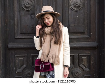 Beautiful stylish young brunette woman in winter beige coat with scarf and hat stands against the background of an old dark wooden door. Fashionable European girl