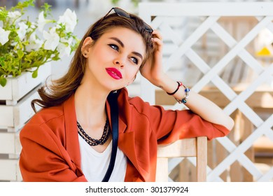 Beautiful stylish young friendship girl  sitting in summer restaurant  and  dreaming.  Happy sunny summer vacation mood, bright colors. Have full red lips and big blue eyes.