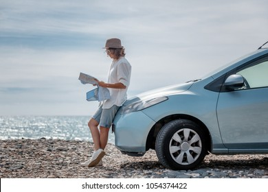 Beautiful stylish young girl travels by car, with a hat and with a card in her hands, summer travel, freedom,