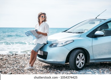 Beautiful stylish young girl travels by car, with a hat and with a card in her hands, summer travel, freedom, transport for rent, new impressions and adventure, freedom and youth