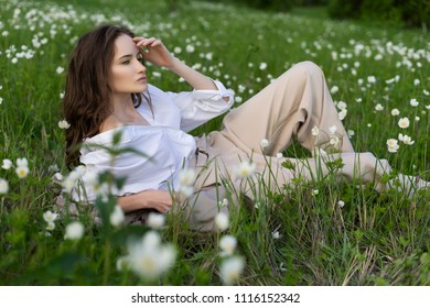 Beautiful stylish young girl wearing a trendy white shirt, beige bloomers, and a pareo lies relaxing on the green grass among the wild flowers. Commercial and advertisement design. Copy space.