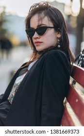 Beautiful stylish young girl wearing glasses in a rumble in the old town, drinking coffee and having fun