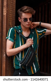 Beautiful stylish young man with sunglasses in a fashionable shirt with a bag near the wooden wall