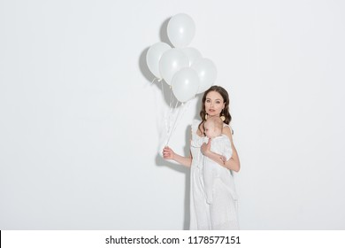 beautiful stylish young mother holding white balloons, carrying adorable infant daughter and looking at camera on grey