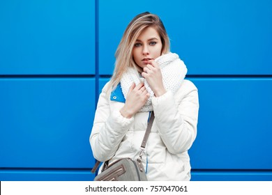 Beautiful stylish young woman with fashionable white knitted scarf and winter warm jacket near the blue wall
