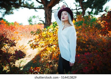beautiful stylish young woman (girl) in dressshirt and hat on red leaves background