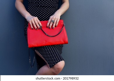 802c4e77 beautiful stylish young woman hold red clutch in hand and black dress near  gray wall.