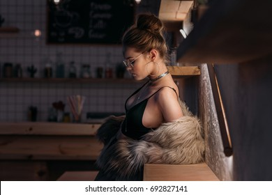 beautiful stylish young woman posing in black sexy clothes and fur coat
