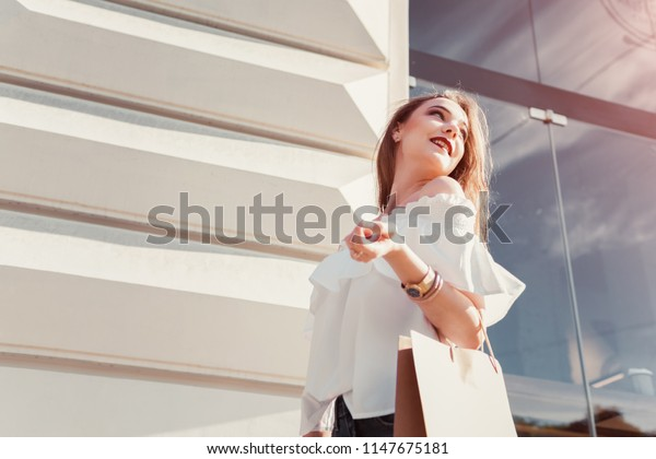 Beautiful stylish young woman with shopping bags walking on city street in summer. Happy girl holding purchases