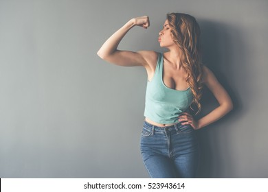 Beautiful stylish young woman is showing her muscles and sending kiss, on gray background