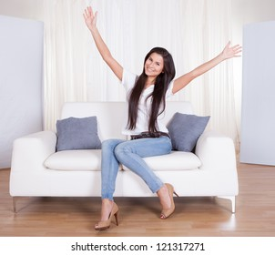 Beautiful stylish young woman sitting on a couch in her living room with her arms thrown wide open smiling happily