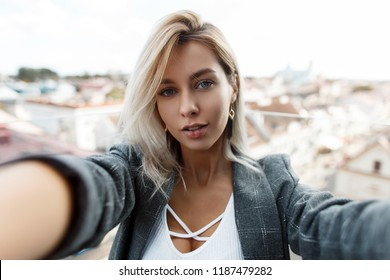 Beautiful stylish young woman in a vintage fashion coat is traveling and photographing on the roof of the city. Girl makes selfie