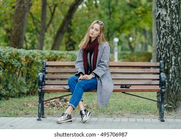 Beautiful stylish young woman in a warm scarf blue jeans trendy shoes and cozy coat sitting alone on bench waiting in fall city park