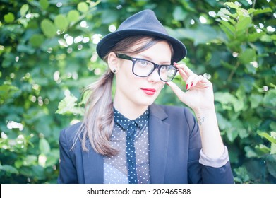 A beautiful stylish young woman's portrait in a garden, touching her black glasses.