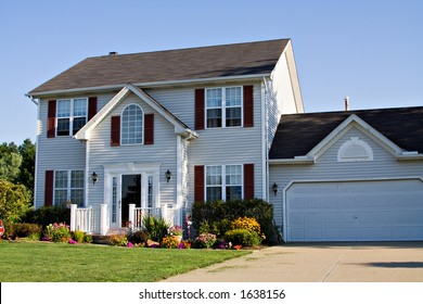 Beautiful suburban family home in summer - flowers decorate yard.