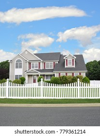 Beautiful Suburban Grey McMansion Home with white fence blue sky clouds USA
