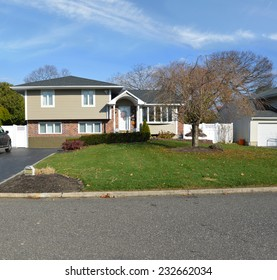 Beautiful suburban high ranch home autumn day residential neighborhood blue sky clouds USA