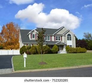 Beautiful Suburban McMansion home blue sky clouds USA