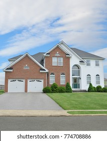 Beautiful suburban McMansion Home with two car garage blue sky clouds USA