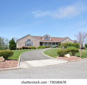 Beautiful Suburban Ranch style home with curved driveway blue sky clouds USA