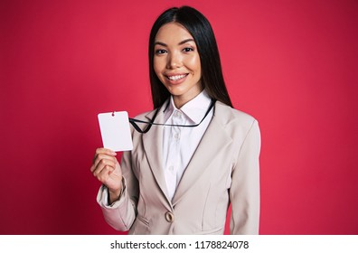 Beautiful success asian woman shows on camera her badge and smiling over pink wall