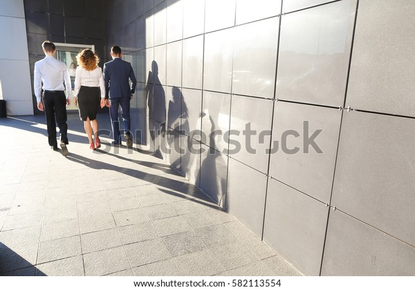 Beautiful successful energetic people, confident, two guys and girl, young businessmen, students go forward, back to camera, smiling on background of gray wall outdoors business center. One of guys