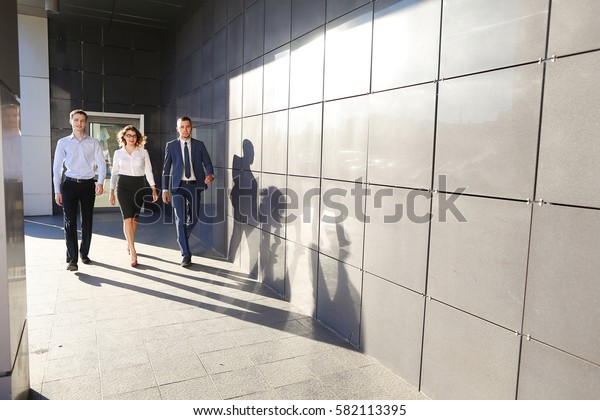 Beautiful successful energetic people, two guys and girl, young businessmen, students confident step forward, smiling and looking at camera on background of gray wall outdoors business center. One of