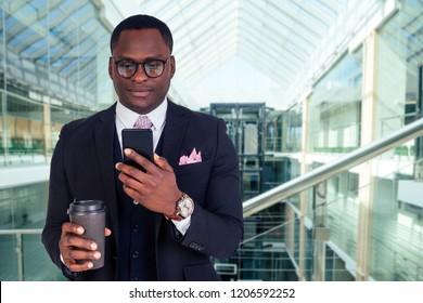 beautiful and successful Latin American business man in a stylish suit well-dressed holds a cup of coffee to go and phone inside the business center office . dark-skinned boss of corporation