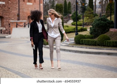 Beautiful and successful women walking and talking. Women wearing suits. One woman is black.