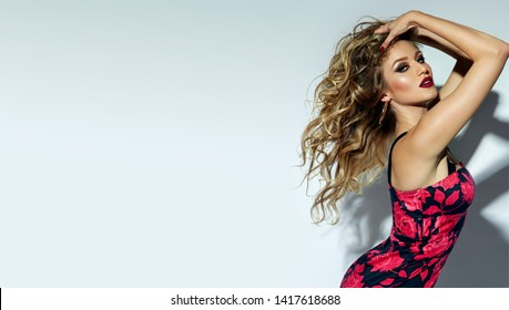 A beautiful, sultry, bright southern girl with a tanned body, in a bright dress with roses, lifts her lush long hair and poses for the camera on a white background.