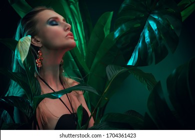 Beautiful sultry woman with wet hair stands among tropical plants. Beauty, fashion and cosmetics concept. Vacation in tropical countries.