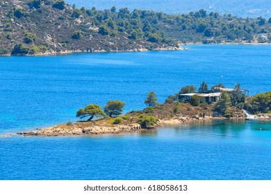 Beautiful summer Aegean Sea coast landscape (near Lagonisi , Sithonia, Halkidiki, Greece). People urecognizable.