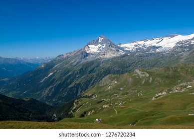 Beautiful summer alpine landscape with snow-covered mountains,green pastures, high alpine valley and  mountain serpentine road  through it, Vanoise National Park, French Alps.