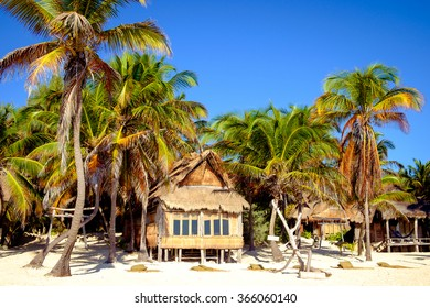 Beautiful summer beach landscape with wooden cabin and palm trees, Tulum, Mexico