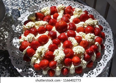 Beautiful summer cake with strawberries and cream outdoors on a table