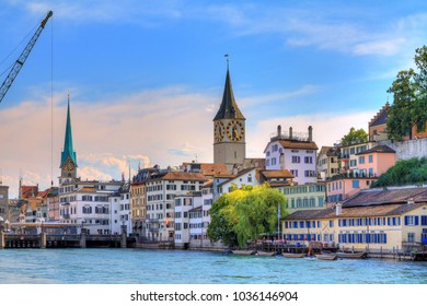Beautiful summer cityscape of the city Zurich, Switzerland, with the big crane at the river Limmat and the Fraumünster and St. Peter Churches