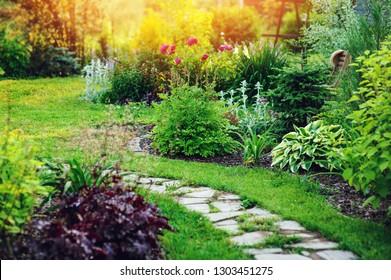 schöner Blick auf den Sommerhüttengarten mit Steinweg und blühenden Perennials
