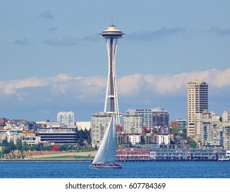 Beautiful summer day on Elliott Bay in Seattle, Washington with a sailboat on the water floating by a couple of Seattle's landmarks from the 1962 World's Fair: Seattle Center arches and Space Needle.