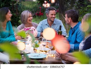Beautiful summer evening in the garden, a group of friends in their forties have a good time laughing together around a table.